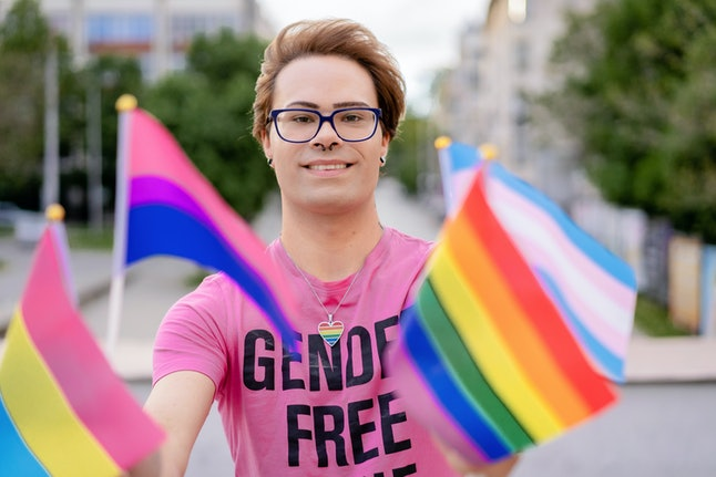 LGBTQ+ activist holding different flags of LGBTQI community defending the human rights, looking at c...