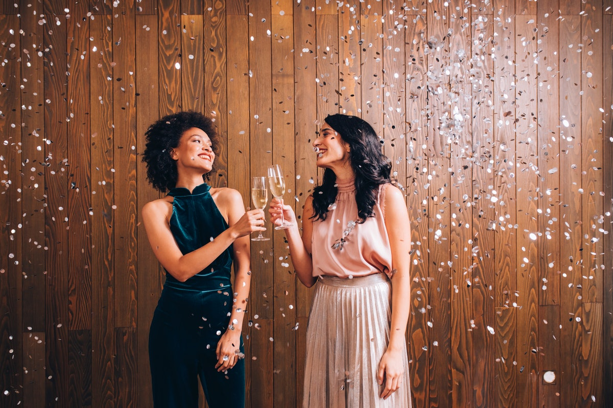 Two young woman posing in their New Year's Eve outfits clinking champagne.