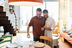 Gay Couple flirting while setting the table for guests