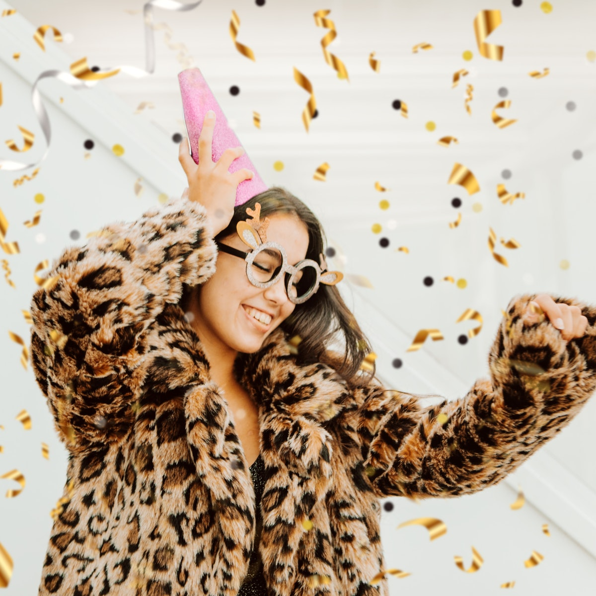 A young woman dancing in a gorgeous New Year's Eve dress and leopard print coat, thinking of the best Instagram caption for her dress.