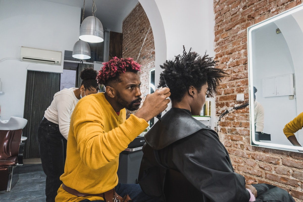 Black brazilian hairstylist with bright pink tips in his hair and wearing a yellow sweater cutting a Black woman's hair