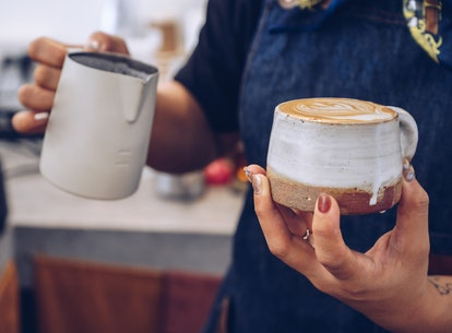 A woman making a latte. Caffeine can only do so much to wake people up and help them process information.