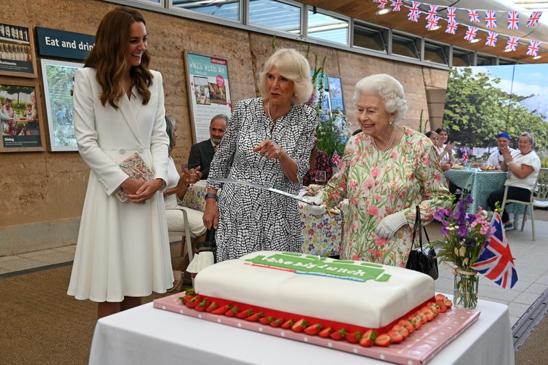 ST AUSTELL, ENGLAND - JUNE 11: Queen Elizabeth II (C) considers cutting a cake with a sword, lent to her by The Lord-Lieutenant of Cornwall, Edward Bolitho, to celebrate of The Big Lunch initiative at The Eden Project during the G7 Summit on June 11, 2021 in St Austell, Cornwall, England. UK Prime Minister, Boris Johnson, hosts leaders from the USA, Japan, Germany, France, Italy and Canada at the G7 Summit. This year the UK has invited India, South Africa, and South Korea to attend the Leaders' Summit as guest countries as well as the EU. (Photo by Oli Scarff - WPA Pool / Getty Images)