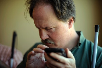 Chip Johnson is checking facebook with Voice Over system in iphone at the Colorado Center for the Bl...