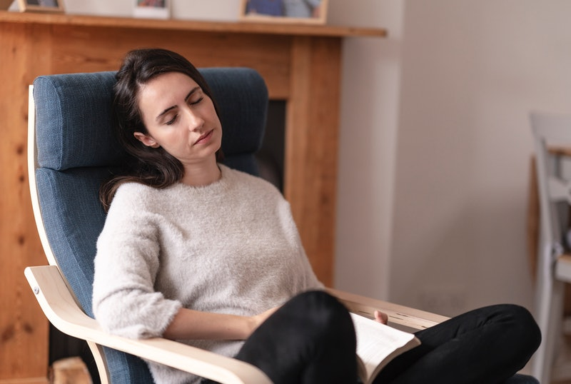Young woman relaxing on the seat, she is falling asleep while reading a book
