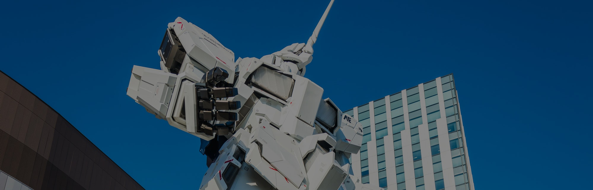 Tourists and shoppers dwarfed by the giant Unicorn Gundam statue outside DiverCity Tokyo Plaza mall on the popular leisure district of Odaiba in Tokyo harbour, Japan.