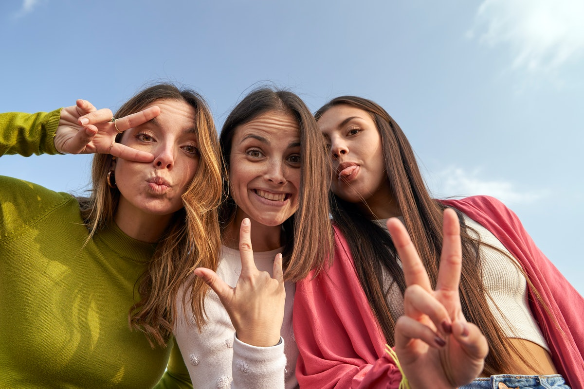 Three best friends with middle hair parts smiling and throwing peace signs at the camera