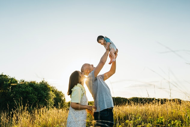 Father throwing up to the air and playing with his three months old son on the countryside