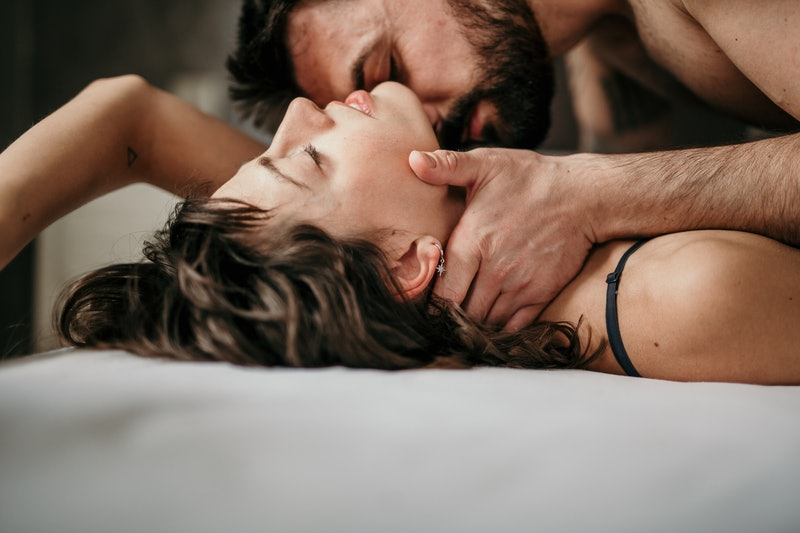 Side view photo of a beautiful couple in bed, being gentle and sensual. Handsome guy with a beard on...