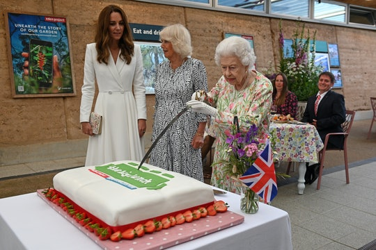 Queen Elizabeth cuts a cake with a sword lent to her by The Lord-Lieutenant of Cornwall on June 11 i...