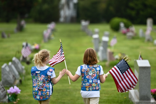 Girl Scout Daisy Troop 1080 place flags on the graves