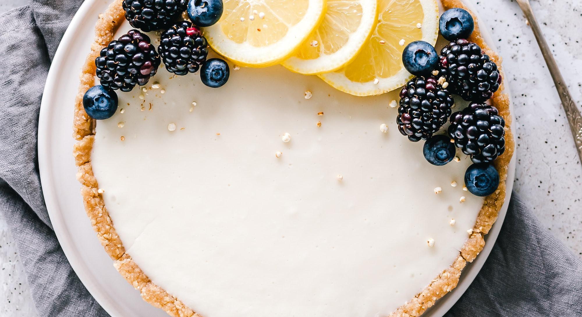 lemon tart with blueberries and fresh lemon garnish, shot from above