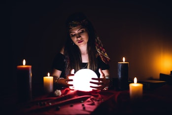 Young caucasian woman fortune teller and crystal sphere.