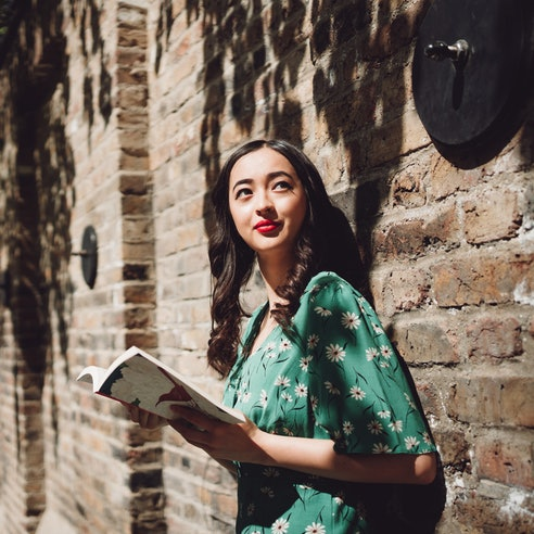 Cheerful beautiful young Asian Brazilian mixed women looking up to the sky while holding a novel on the street of London.