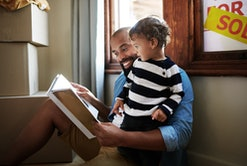 Shot of a young father reading a picture book to his toddler while resting against the window with a sold sign on it