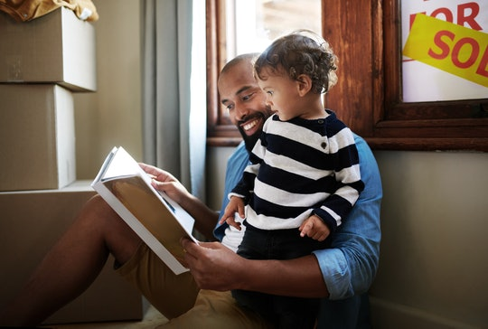 Shot of a young father reading a picture book to his toddler while resting against the window with a...
