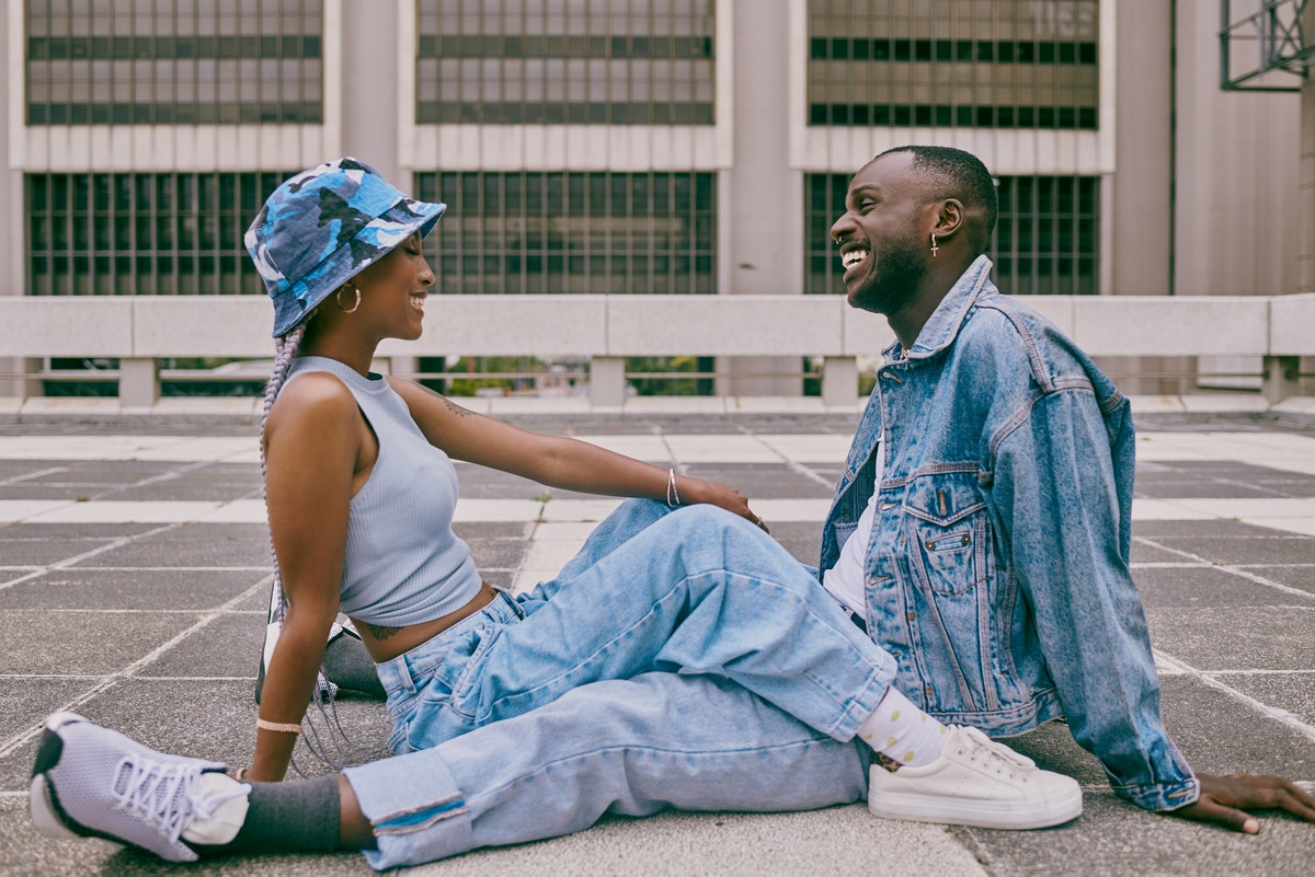 A trendy young Black couple sitting on the ground wearing trendy, baggy denim jeans and a denim jacket