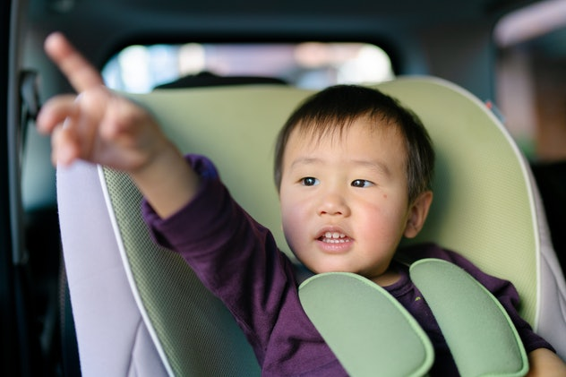 A small baby boy is sitting in a safety seat of a rear seat on a car, pointing out the window.
