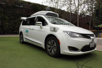 A Waymo self-driving car pulls into a parking lot at the Google-owned company's headquarters in Moun...