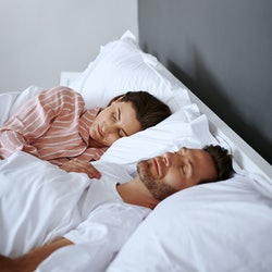 """A couple sleeps together, looking unhappy.  Wondering, """"why can't i fall asleep with my boyfriend?"""" These 7 issues might be to blame."""