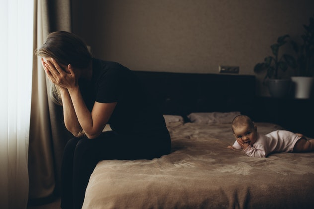 woman holding head in hands while baby crawls on bed