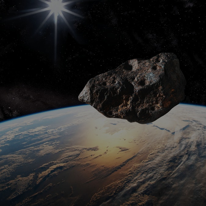 """Where: Studio/office – Chino Hills, CA USA When: 6-1-2020 Who/What: The represented asteroid is my studio photograph of an actual (3"""" long) meteorite, and I added impact craters with PhotoShop to simulate a larger scaled-up asteroid.  Earth NASA URL- https://www.nasa.gov/sites/default/files/thumbnails/image/iss064e053054.jpg The sky area was created with PhotoShop layering of my time-exposure photographs of stars and added to simulate outer space."""