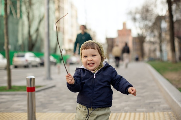 Beautiful little girl in the blue jacket and knit hat walks down the sidewalk and looks away. She sm...