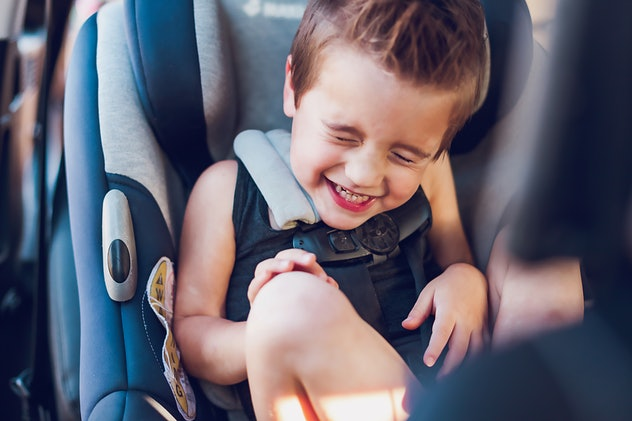 little boy laughing in his car seat