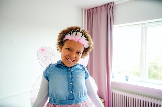 Shot of a little girl wearing fairy wings and a crown while playing in her bedroom