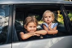 two little girls looking out the window of a parked car