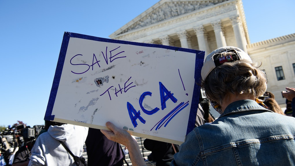 A demonstrator holds a sign in front of the US Supreme Court in Washington, DC, on November 10, 2020...