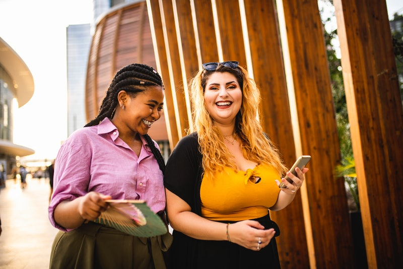 Two women walk in the city, proud to have found body positivity, neutrality, and acceptance. What's ...