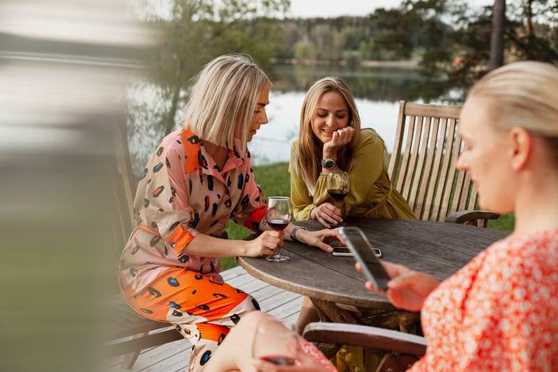 A group of women drink wine at a lake house. As the pandemic has ended, social drinking has resumed —but people are finding drinking affects them differently than it did a year ago.
