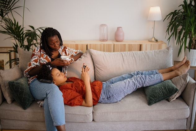 The daughter lies in her mother's lap and uses a mobile phone while her mother watches TV