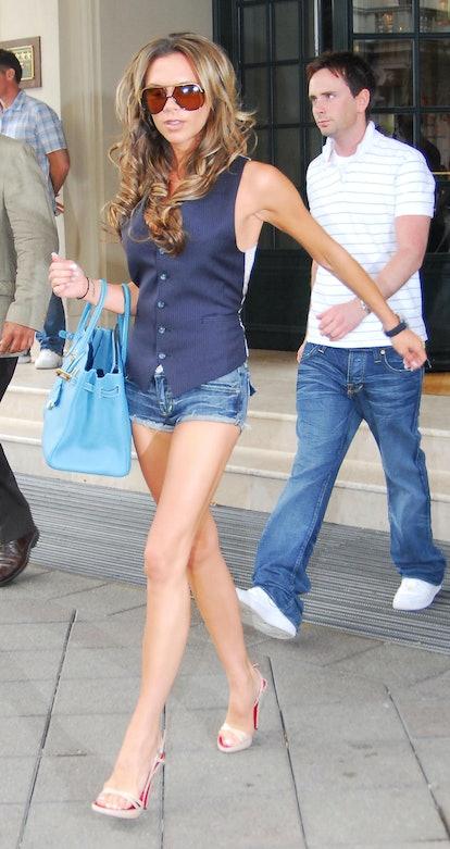 Victoria Beckham wearing waistcoat shorts big sunglasses at the 2006 World Cup