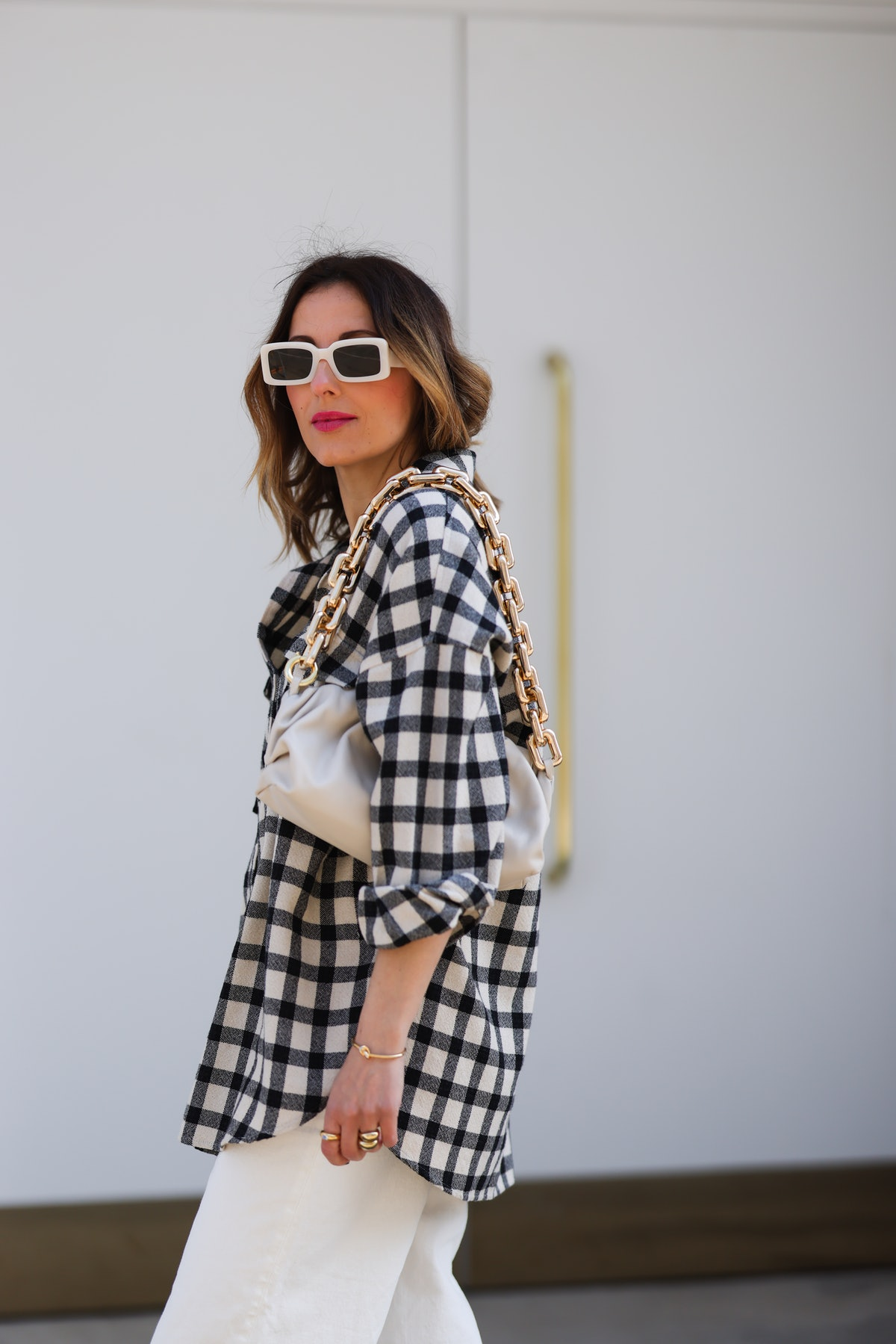 Elise Soho walking in the street and wearing a black and white Checkerboard Shirt