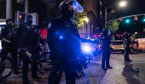 PORTLAND, OR - APRIL 20: Portland police stand guard as tensions rise with a small group of protesters on April 20, 2021 in Portland, United States. Former police officer Derek Chauvin was on trial on second-degree murder, third-degree murder and second-degree manslaughter charges in the death of George Floyd May 25, 2020.  After video was released of then-officer Chauvin kneeling on Floyds neck for nine minutes and twenty-nine seconds, protests broke out across the U.S. and around the world. The jury found Chauvin guilty on all three charges.  ( Photo by Paula Bronstein/Getty Images)