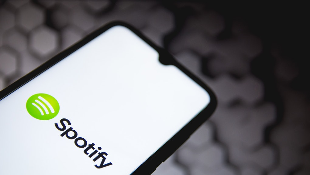In this photo illustration a Spotify logo seen displayed on a smartphone screen with a computer wallpaper in the background in Athens, Greece on May 5, 2021. (Photo by Nikolas Kokovlis/NurPhoto via Getty Images)