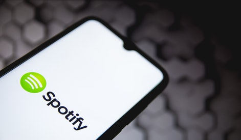 In this photo illustration a Spotify logo seen displayed on a smartphone screen with a computer wall...