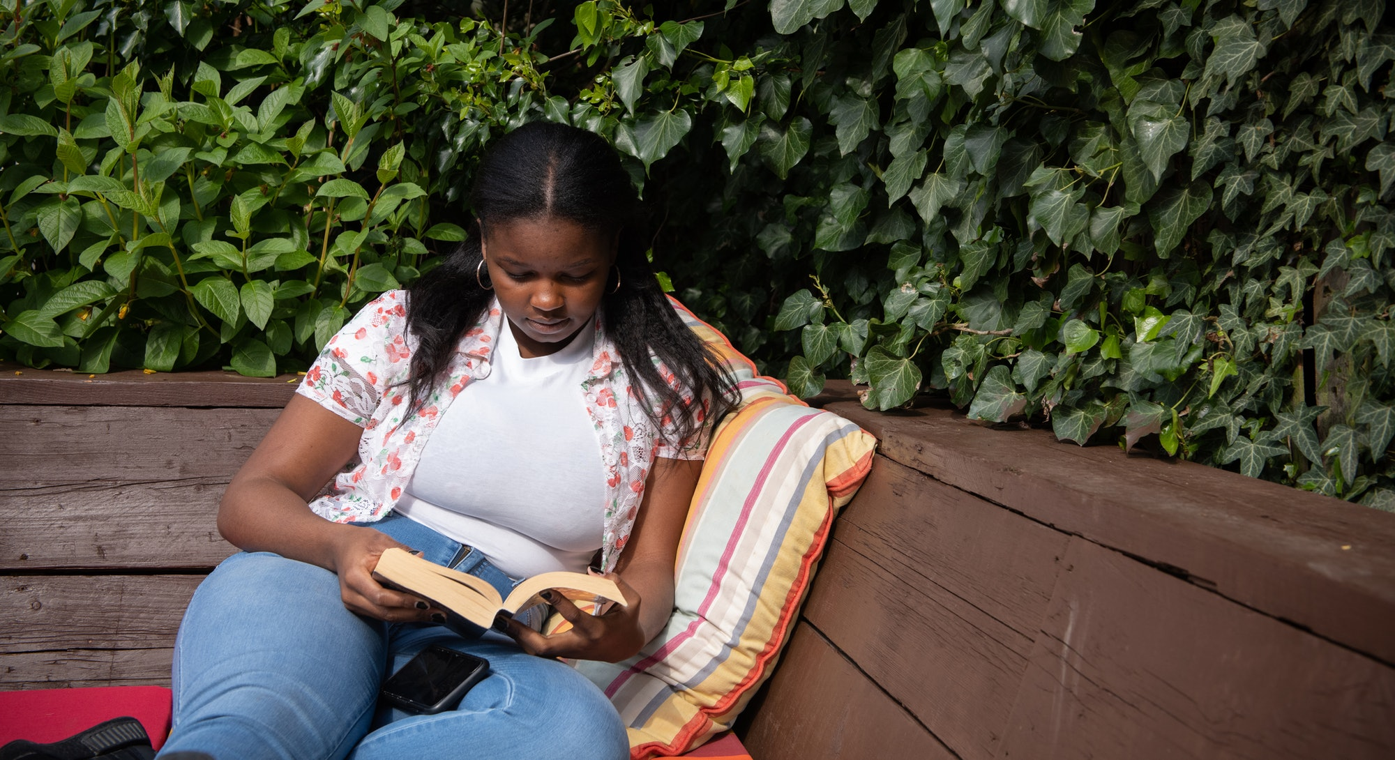 Young woman sitting on a deck in the garden reading a book