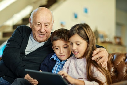 kids and their grandfather looking at a tablet together