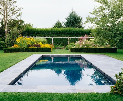 a beautifully landscaped pool with raised garden beds