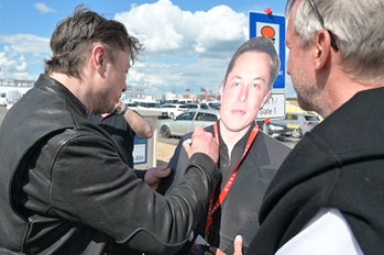 17 May 2021, Brandenburg, Grünheide: Elon Musk (l), Tesla CEO, stands on the construction site of the Tesla factory and signs a cardboard display of himself. He has taken a look at the progress of construction of the new factory in Grünheide near Berlin, which will probably start production several months later than originally planned. The 49-year-old did not initially comment on Monday. Photo: Christophe Gateau/dpa (Photo by Christophe Gateau/picture alliance via Getty Images)