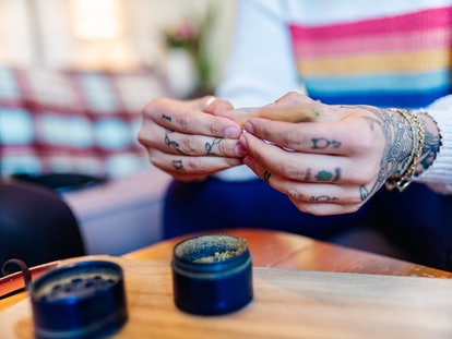 Young woman with tattoos rolls a cannabis joint. Smoking dabs can lead to side effects like increase...