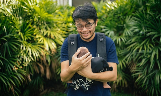 dad smiling at newborn baby in carrier