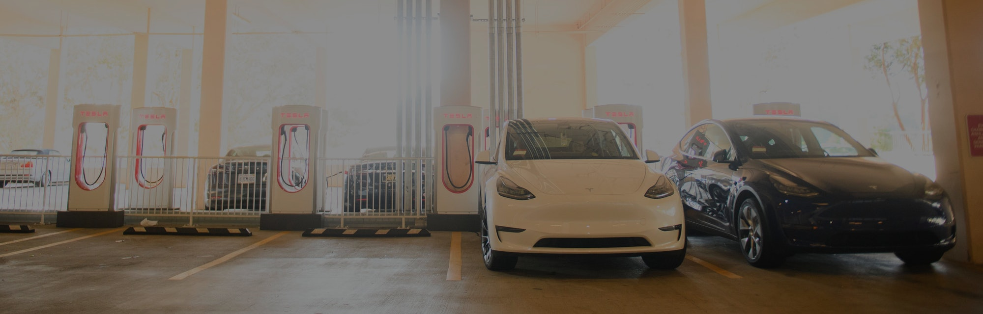 Tesla Inc. electric vehicles charge at the company's supercharger station inside a parking garage on January 4, 2021 in Hermosa Beach, California. - After shares rocketed higher in 2020 on surging auto deliveries, Tesla enters 2021 with plenty of momentum even as its vision of taking electric cars mainstream remains a way off. (Photo by Patrick T. Fallon / AFP) (Photo by PATRICK T. FALLON/AFP via Getty Images)