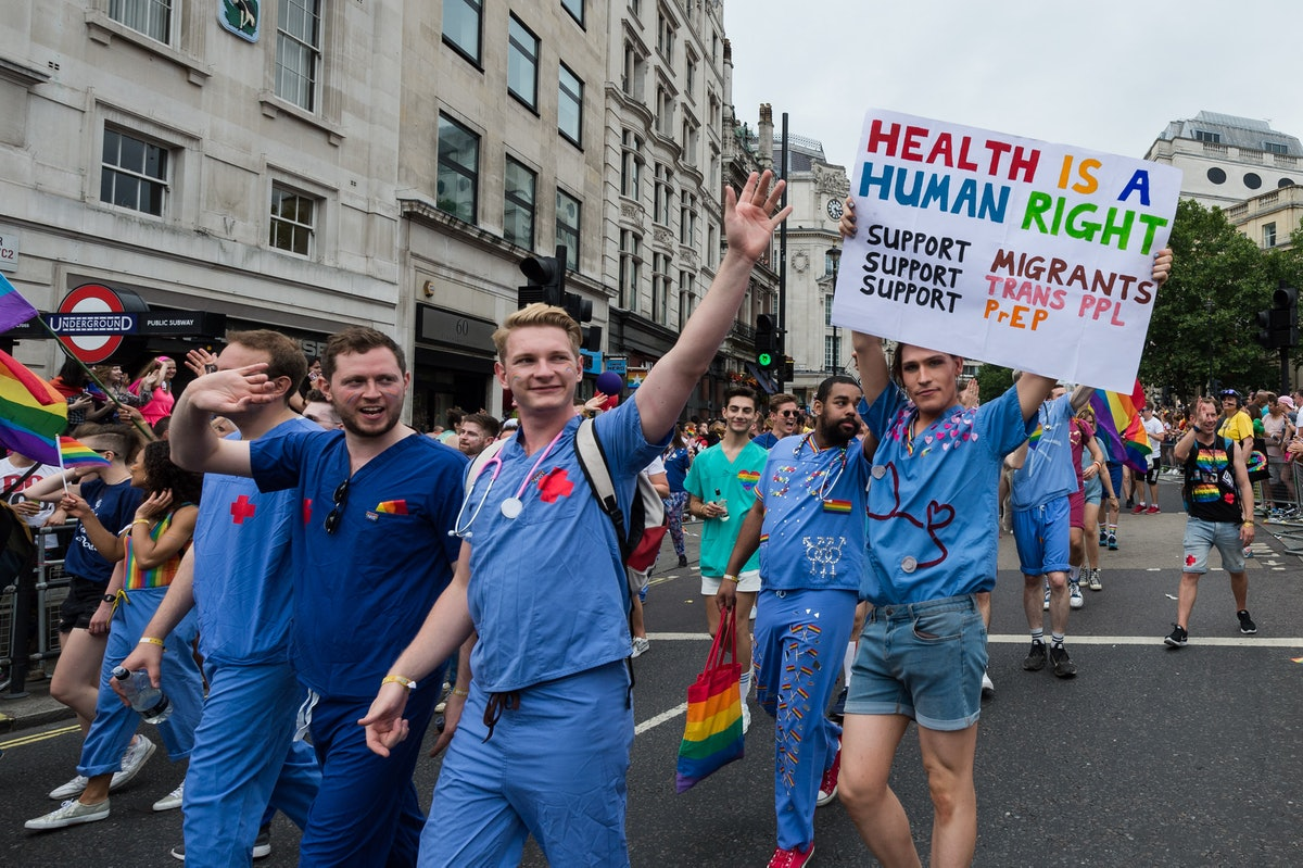 """NHS doctors take part in the 2019 Pride parade in London parade, carrying rainbow flags and a sign reading """"health is a human right"""""""
