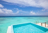 Infinity swimming pool by beach at the modern luxury hotel. Luxurious summer vacation or holiday concept