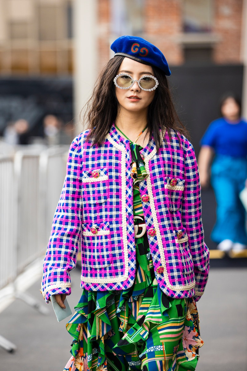 MILAN, ITALY - SEPTEMBER 22:  A guest, wearing a printed maxi dress, pink and blue decorated jacket,...