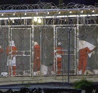 """(FILES) This file photo shows detainees as they prepare themselves for the evening prayer 04 March 2002 at Camp X-Ray in Guantanamo Bay, Cuba by facing towards Mecca.  Some 300 detainees from Afghanistan are being held at the US Naval Base in Guantanamo Bay, Cuba. Syria implicitly denied 24 September 2003, any involvement in an alleged case of spying at the US detention center for Afghan war prisoners in Guantanamo Bay, Cuba. New Syrian Information Minister Ahmad al-Hassan, speaking at his first meeting with journalists in Damascus, was responding to US media reports that Ahmad al-Halabi, a US military translator at Guantanamo, was working for Syrian intelligence. Calling the allegations """"baseless and illogical"""", Hassan demanded, """"How could Syria have spies in Guantanamo? Is the CIA incapable of finding a trustworthy translator?"""" The Pentagon said Halabi, a senior airman, was detained July 23 on his return from the base at Guantanamo.   AFP PHOTO/Peter MUHLY (Photo by PETER MUHLY / AFP) (Photo by PETER MUHLY/AFP via Getty Images)"""